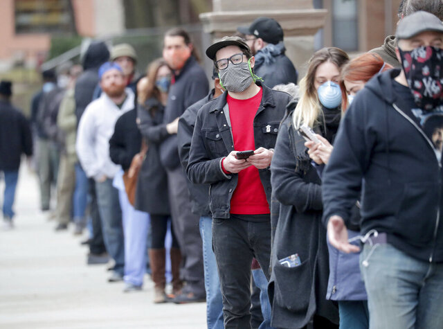People line up to vote at Riverside High School during the primary in Milwaukee on Tuesday, April 7, 2020. Voters lined up to cast ballots across Wisconsin on Tuesday, ignoring a stay-at-home order in the midst of the coronavirus pandemic to participate in the state's presidential primary election. (Mike De Sisti/Milwaukee Journal-Sentinel via AP)