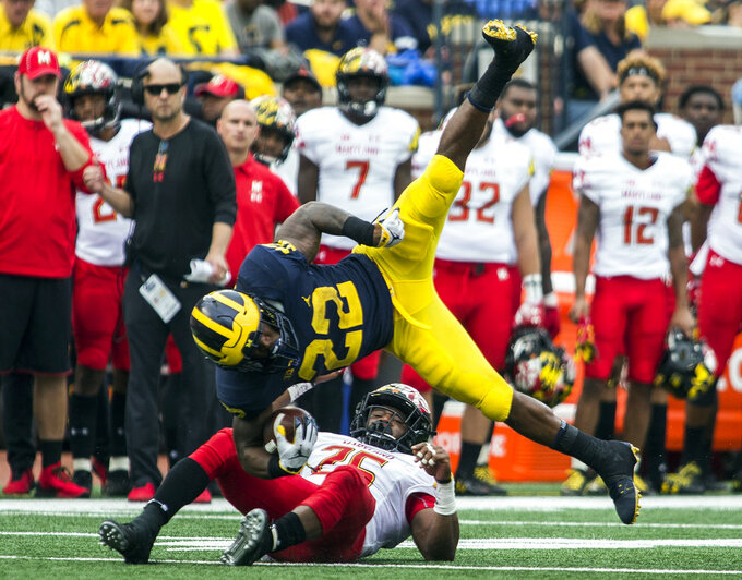 Michigan running back Karan Higdon (22) gets upended by Maryland defensive back Antoine Brooks Jr. (25) in the third quarter of an NCAA college football game in Ann Arbor, Mich., Saturday, Oct. 6, 2018. Michigan won 42-21. (AP Photo/Tony Ding)