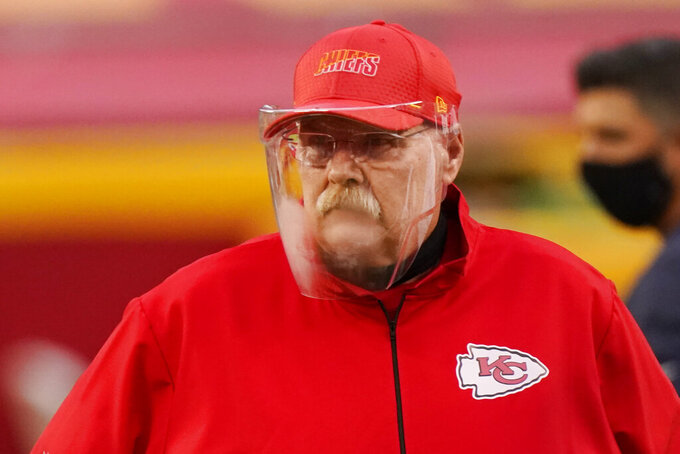 Kansas City Chiefs head coach Andy Reid wears a face shield as he watches players warm up before an NFL football game against the Houston Texans Thursday, Sept. 10, 2020, in Kansas City, Mo. (AP Photo/Charlie Riedel)