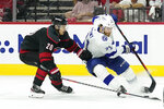 Carolina Hurricanes center Sebastian Aho (20) chases Tampa Bay Lightning center Brayden Point (21) during the third period in Game 5 of an NHL hockey Stanley Cup second-round playoff series in Raleigh, N.C., Tuesday, June 8, 2021. (AP Photo/Gerry Broome)