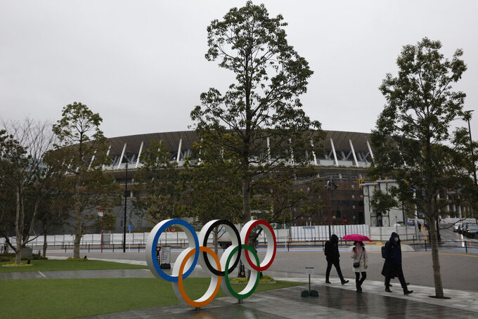 People walk past the Olympic rings near the New National Stadium in Tokyo, Wednesday, March 4, 2020. The Tokyo Olympics are being threatened by a fast-spreading virus that has shut down most schools, sports competitions and Olympic-related events in Japan. (AP Photo/Jae C. Hong)