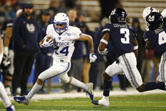 Air Force running back Kadin Remsberg, left, runs around the corner for a short gain as Utah State safety Troy Lefeged Jr. pursues in the first half of an NCAA college football game Saturday, Oct. 26, 2019, at Air Force Academy, Colo. (AP Photo/David Zalubowski)