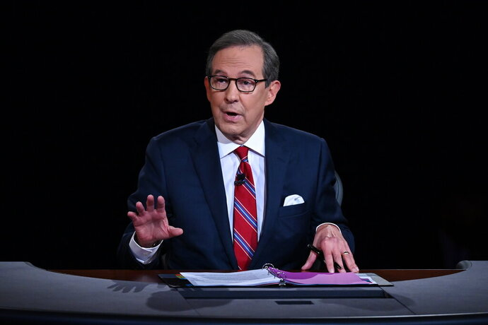 FILE - Moderator Chris Wallace of Fox News speaks as President Donald Trump and Democratic presidential candidate former Vice President Joe Biden participate in the first presidential debate in Cleveland on Sept. 29, 2020. Leaders of the Commission on Presidential Debates and moderators of all three debates gathered for a remote debrief Monday night. Two takeaways: increased early voting means the commission is considering earlier debates, and the mute button may be here to stay.  (Olivier Douliery/Pool via AP, File)