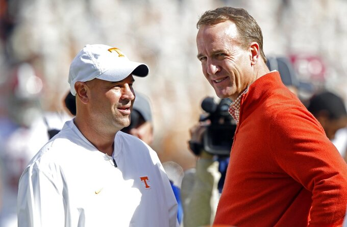 Tennessee head coach Jeremy Pruitt talks with former Tennessee quarterback Peyton Manning before an NCAA college football game against Alabama, Saturday, Oct. 20, 2018, in Knoxville, Tenn. (AP Photo/Wade Payne)