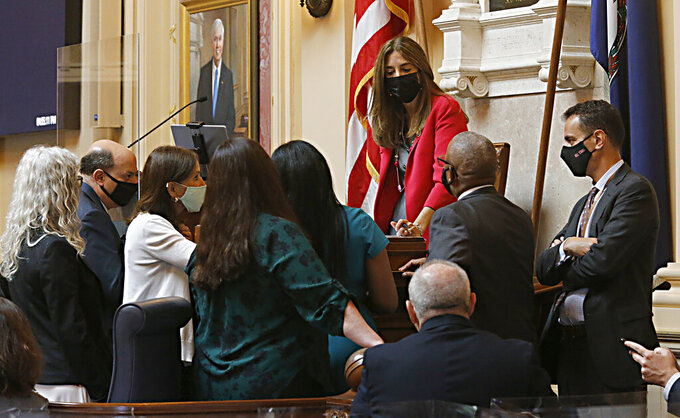 House staff and Democratic members of the House of Delegates gather around the desk of Speaker Eileen Filler-Corn, D-Fairfax, center, before the budget bill was voted on at the Virginia State Capitol in Richmond, Va., Tuesday, Aug. 3, 2021, on the second day of the General Assembly Special Session. (Bob Brown/Richmond Times-Dispatch via AP)
