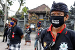 Security guards wearing face masks lineup during a briefing at the opening of Kuta beach in Bali, Indonesia, Thursday, July 9, 2020. Indonesia's resort island of Bali reopened after a three-month virus lockdown Thursday, allowing local people and stranded foreign tourists to resume public activities before foreign arrivals resume in September. (AP Photo/Firdia Lisnawati)
