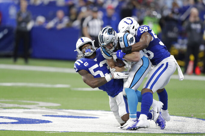 Carolina Panthers' Christian McCaffrey (22) is tackled by Indianapolis Colts' Darius Leonard (53) and Bobby Okereke (58) during the second half of an NFL football game, Sunday, Dec. 22, 2019, in Indianapolis. (AP Photo/Michael Conroy)