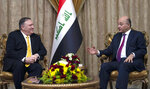 FILE - In this Jan. 9, 2019 file photo, US Secretary of State Mike Pompeo, left, meets with Iraqi President Barham Salih, in Baghdad, Iraq. Iraq is seeking to reclaim a leadership role in the Arab world after decades of conflict. It is focusing on a centrist policy and its top leaders are determined to maintain good relations with both Iran and the United States. (Andrew Caballero-Reynolds/Pool, File)