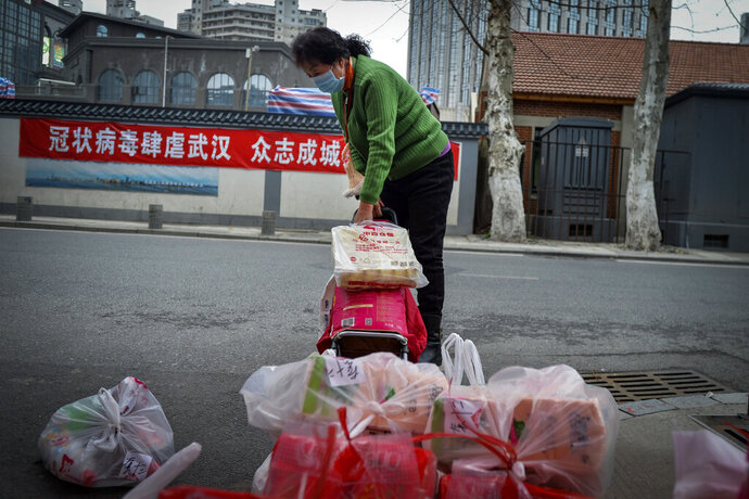 In this Saturday, Feb. 22, 2020, photo, a woman using a trolley bag to collect foods distributed by volunteers outside her home in Wuhan in central China's Hubei province. South Korea and China both reported a rise in new virus cases on Sunday, as the South Korean prime minister warned that the fast-spreading outbreak linked to a local church and a hospital in the country's southeast had entered a