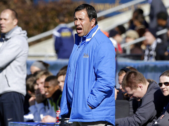 FILE - In this Dec. 14, 2014 file photo, UCLA coach Jorge Salcedo reacts during the first half of an NCAA College Cup championship soccer game against Virginia in Cary, N.C. Salcedo was charged along with nearly 50 other people Tuesday, March 12, 2019, in a scheme in which wealthy parents bribed college coaches and insiders at testing centers to get their children into some of the most elite schools in the country, federal prosecutors said. UCLA said that Salcedo has been placed on leave pending a review and will have no involvement with the team.  (AP Photo/Gerry Broome, File)