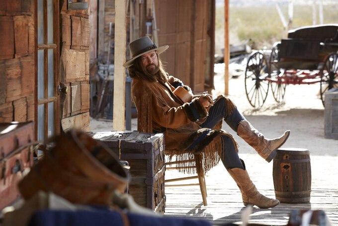 """This undated photo provided by Doritos shows Billy Ray Cyrus in a scene from the company's 2020 Super Bowl NFL football spot. The snack chip is betting people will connect with """"Old Town Road,"""" the smash hit of the summer by Lil Nas X. In the Western-themed ad Lil Nas has a dance off with grizzled character actor Sam Elliott. Billy Cyrus, who features in the song's remix, also makes a cameo. (Doritos via AP)"""