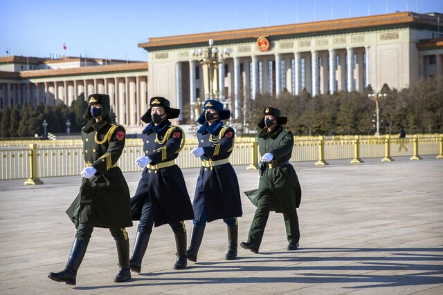 FILE - In this Feb. 4, 2020, file photo, members of a Chinese honor guard wear face masks as they march in formation near the Great Hall of the People on Tiananmen Square in Beijing. China's ruling Communist Party faces a politically fraught decision: Admit the outbreak of a new virus isn't under control and cancel this year's highest-profile official event. Or bring 3,000 legislators to Beijing next month and risk fueling public anger at the government's handling of the disease. (AP Photo/Mark Schiefelbein, File)