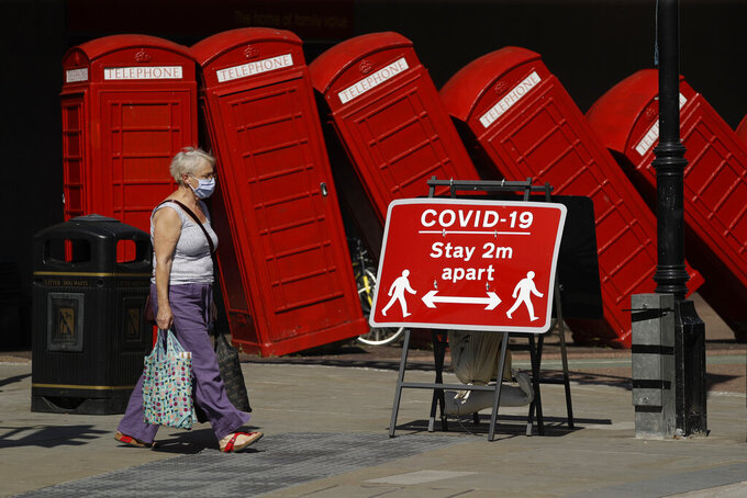"""A sign requesting people stay two meters apart to try to reduce the spread of COVID-19 is displayed in front of """"Out of Order,"""" a 1989 sclupture made of red telephone boxes by British artist David Mach, in Kingston upon Thames, southwest London, Monday, June 22, 2020. (AP Photo/Matt Dunham)"""