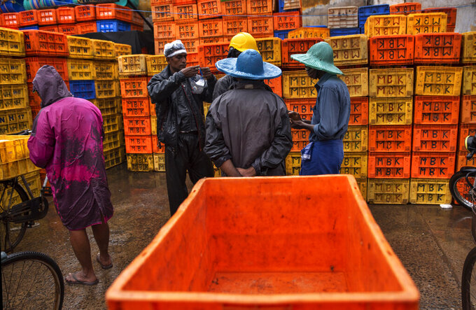 A man prepares to wear his mask as fish vendors chat on a rainy day in Kochi, Kerala state, India, Monday, June 22 2020. India is the fourth hardest-hit country by the COVID-19 pandemic in the world after the U.S., Russia and Brazil. (AP Photo/R S Iyer)