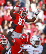Georgia wide receiver Tyler Simmons gets a hoist from Isaiah Wilson after scoring a touchdown against Massachusetts during the first half of an NCAA college football game, Saturday, Nov. 17, 2018, in Athens, Ga. (Curtis Compton/Atlanta Journal-Constitution via AP)