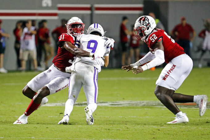 Furman's Hamp Sisson (9) is trapped by North Carolina State's Vi Jones (31) and Ibrahim Kante (52) during the second half of an NCAA college football game in Raleigh, N.C., Saturday, Sept. 18, 2021. (AP Photo/Karl B DeBlaker)