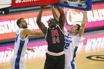 Nebraska's Yvan Ouedraogo (24) goes to the basket against Creighton's Ryan Kalkbrenner (32) and Mitch Ballock, left, during the first half of an NCAA college basketball game in Omaha, Neb., Friday, Dec. 11, 2020. (AP Photo/Nati Harnik)