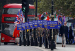 Anti Brexit protestors show their posters in front of parliament in London, Wednesday, Oct. 23, 2019.  Britain's government is waiting for the EU's response to its request for an extension to the Brexit deadline. (AP Photo/Frank Augstein)