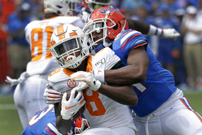 Tennessee running back Ty Chandler, left, is stopped by Florida linebacker James Houston IV after a short gain during the second half of an NCAA college football game, Saturday, Sept. 21, 2019, in Gainesville, Fla. (AP Photo/John Raoux)