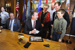 FILE - In this April 16, 2019, file photo, Luke Phipps, 12, presents Montana Gov. Steve Bullock with a fossilized rib and tail vertebrae from a triceratops at the state Capitol in Helena, Mont., after the governor signed a bill to clarify that fossils are part of a property's surface rights, not its mineral rights, unless a contract separating the ownership says otherwise. The Montana Supreme Court heard arguments Thursday, Nov. 7, 2019, on the same issue in relation to a 2014 court case over the ownership of millions of dollars of dinosaur fossils that is not affected by the new law. (Thom Bridge/Independent Record via AP, File)