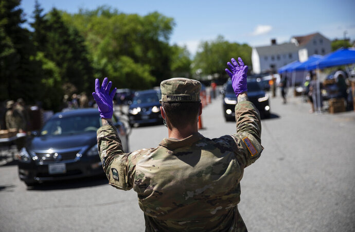 A member of the Rhode Island National Guard directs motorists as volunteers with the Dairy Farmers of America distribute free milk to families in need, Wednesday, May 27, 2020, in Pawtucket, R.I. Dairy farmers have a milk surplus because demand has dropped as schools and restaurants closed during the coronavirus pandemic, and some farmers have had to pour excess milk away. Farmers donated the 4,300 gallons of milk given away today at McCoy Stadium. (AP Photo/David Goldman)