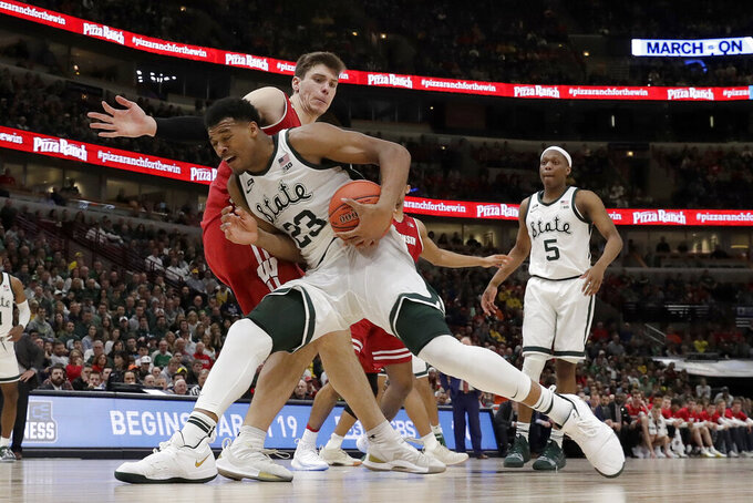 Michigan State's Xavier Tillman (23) drives against Wisconsin's Ethan Happ during the second half of an NCAA college basketball game in the semifinals of the Big Ten Conference tournament, Saturday, March 16, 2019, in Chicago. (AP Photo/Nam Y. Huh)
