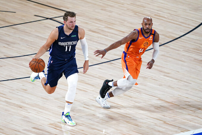 Dallas Mavericks' Luka Doncic (77) brings the ball down the court as Phoenix Suns' Jevon Carter defends during the first half of an NBA basketball game Thursday, Aug. 13, 2020 in Lake Buena Vista, Fla. (AP Photo/Ashley Landis, Pool)