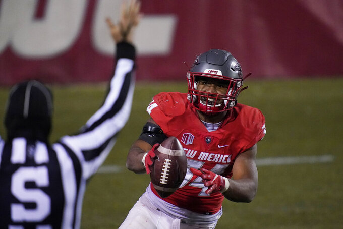New Mexico running back Bobby Cole (34) celebrates after scoring a touchdown against Wyoming during the second half of an NCAA college football game Saturday, Dec. 5, 2020, in Las Vegas. (AP Photo/John Locher)