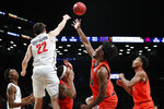 Richmond guard Andre Gustavson (22) passes over Auburn guards Samir Doughty (10) and Preston Cook (14) in the first half of an NCAA college basketball game in the Legends Classic, Tuesday, Nov. 26, 2019, in New York. (AP Photo/Kathy Willens)