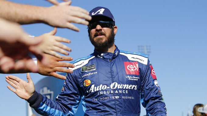 Martin Truex Jr., greets fans during the NASCAR Cup Series race at Martinsville Speedway in Martinsville, Va., Sunday, Oct. 27, 2019. (AP Photo/Steve Helber)