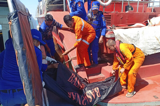 In this photo released by the National Search And Rescue Agency (BASARNAS), rescuers carry the body of a victim of a sunken boat off Bengkalis, Indonesia, Thursday, Jan. 23, 2020. A boat carrying 20 Indonesian migrant workers sank on its way to Malaysia, and rescuers have found 10 survivors and are searching for the missing. (BASARNAS via AP)