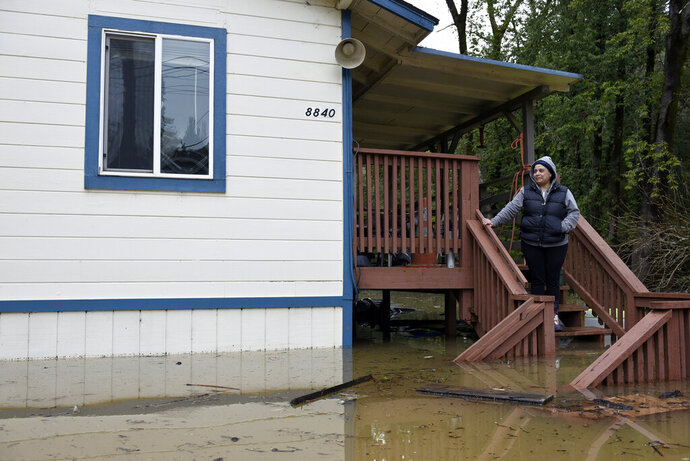 Amanda Hamner looks out at flood waters from the Russian River surrounding her home in Forestville, Calif., on Wednesday, Feb. 27, 2019. The still rising Russian River was engorged by days of rain from western U.S. storms. (AP Photo/Michael Short)