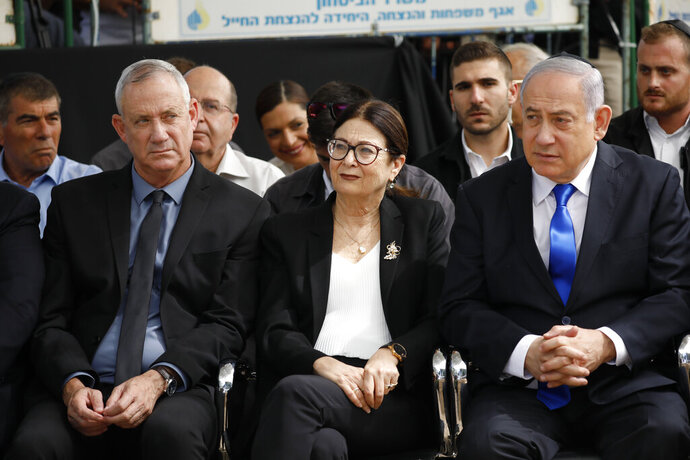 FILE - In this Sept. 19, 2019 file photo, Blue and White party leader Benny Gantz, left, Esther Hayut, the Chief Justice of the Supreme Court of Israel, center, and Israeli Prime Minister Benjamin Netanyahu attend a memorial service for former President Shimon Peres in Jerusalem. Barring a nearly unfathomable about face, Israel is headed Wednesday, Dec. 11 toward an unprecedented third election within a year - prolonging a political stalemate that has paralyzed government and undermined its citizens' faith in the democratic process. (AP Photo/Ariel Schalit, File)