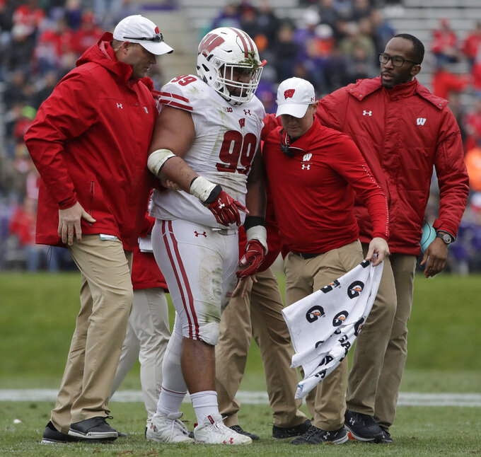 Wisconsin nose tackle Olive Sagapolu is helped after an injury during the second half of an NCAA college football game against Northwestern in Evanston, Ill., Saturday, Oct. 27, 2018. Northwestern won 31-17. (AP Photo/Nam Y. Huh)