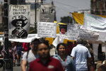 Images of Mexican revolutionary leader Emiliano Zapata hang as part of a demonstration outside the National Palace in Mexico City, Wednesday, April 10, 2019. The sign at left reads in Spanish