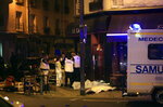 FILE - In this Nov.13, 2015 file photo, medics stand by victims in a Paris restaurant, Friday, Nov. 13, 2015. On Nov. 13, 2015, a cell of nine Islamic State militants armed with automatic rifles and explosive vests left a trail of dead and injured at the national stadium, Paris bars and restaurants and the Bataclan concert hall. Nearly all the attackers were from France or Belgium, as were the cell's 10th member — the only one still alive. He is the chief defendant among 20 people charged in a trial that is expected to last nine months. (AP Photo/Thibault Camus, File)