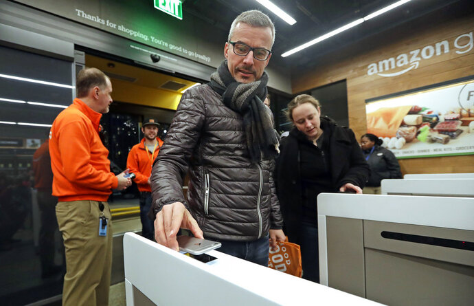 FILE- In this Jan. 22, 2018, file photo a customer scans his Amazon Go cellphone app at the entrance as he heads into an Amazon Go store in Seattle. Microsoft is working on automated checkout technology that could help retailers compete with Amazon's new cashier-less stores. One firm building automated checkout systems, AVA Retail, said Thursday, June 14 that it is working with Microsoft on the technology for physical stores. (AP Photo/Elaine Thompson, File)