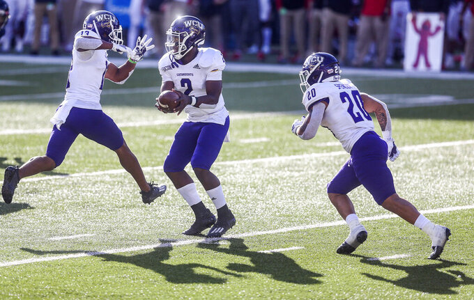 Western Carolina quarterback Mark Wright (2) fakes a handoff to running back Calvin Jones (13) and Donnavan Spencer (20) during the second half of an NCAA football game Saturday, Nov. 14, 2020, in Lynchburg, Va. (AP Photo/Shaban Athuman)