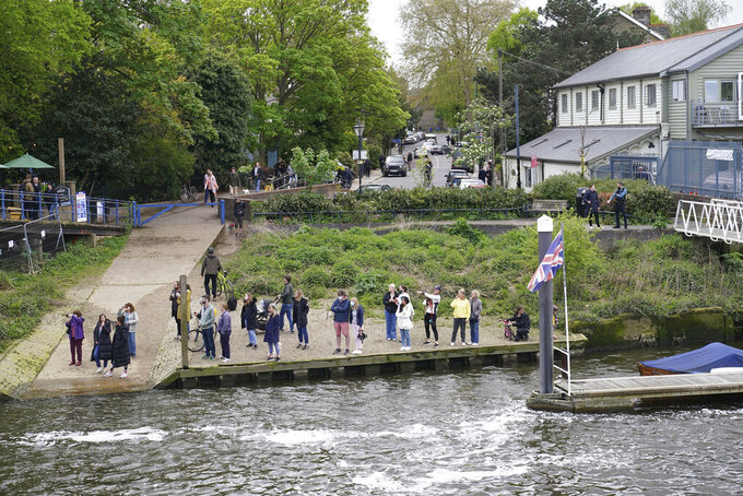 People gather at Teddington Lock to try and spot a Minke whale, which was freed on Sunday after it became stuck on Richmond lock's boat rollers but has remained in the Thames, is seen near Teddington Lock in London, Monday, May 10, 2021. A Port of London Authority spokesperson said a whale had never been seen this far up the Thames before, some 95 miles from its mouth. (Yui Mok/PA via AP)