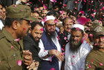 FILE - In this Oct. 19, 2017 file photo, supporters of Hafiz Saeed, center, head of the Pakistani religious party, Jamaat-ud-Dawa, is showered with rose petals by his supporters as he arrives to a court in Lahore, Pakistan. Saeed is India's most wanted man who also has a $10 million U.S.-imposed bounty on his head, lives in Pakistan. Pakistan got a mixed review for its efforts to curb terrorist financing and money laundering as it tries to avoid being blacklisted by the Financial Action Task Force, a global watchdog, when it meets in Paris Wednesday, Oct. 16, 2019. (AP Photo/K.M. Chaudary, File)