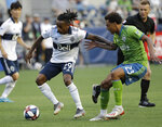 Vancouver Whitecaps' Yordi Reyna (29) tries to control the ball in front of Seattle Sounders' Henry Wingo (23) during the first half of an MLS soccer match Saturday, June 29, 2019, in Seattle. (AP Photo/Elaine Thompson)