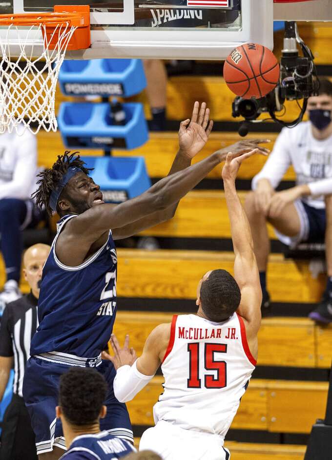 Utah State center Neemias Queta (23) blocks a shot taken by Texas Tech guard Kevin McCullar (15) during the first half of a first round game in the NCAA men's college basketball tournament, Friday, March 19, 2021, in Bloomington, Ind. (AP Photo/Doug McSchooler)