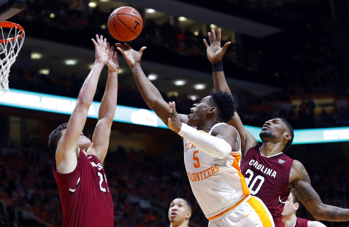 Tennessee guard Admiral Schofield, center, shoots as he's defended by South Carolina forward Maik Kotsar, left, and forward Chris Silva, right, during the second half of an NCAA college basketball game Wednesday, Feb. 13, 2019, in Knoxville, Tenn. Tennessee won 85-73. (AP photo/Wade Payne)