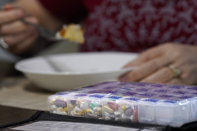 Her regimen of daily pills sit in a container as Kari Wegg finishes her breakfast in her home in Westfield, Ind., on Tuesday, March 23, 2021. (AP Photo/Charles Rex Arbogast)