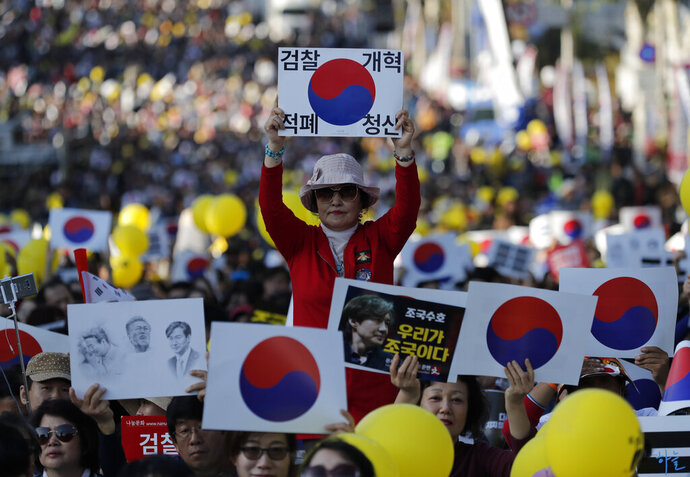 A pro-government supporter holds a sign before a rally supporting Justice Minister Cho Kuk in front of Seoul Central District Prosecutors' Office in Seoul, South Korea, Saturday, Oct. 12, 2019. The letters read