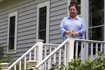 Poet Tammi Truax poses, Wednesday, July 29, 2020, on the front steps of her home in Eliot, Maine. Truax, the poet laureate for Portsmouth, N.H., pens a weekly pandemic poem that is included in the city's COVID-19 newsletter. (AP Photo/Charles Krupa)