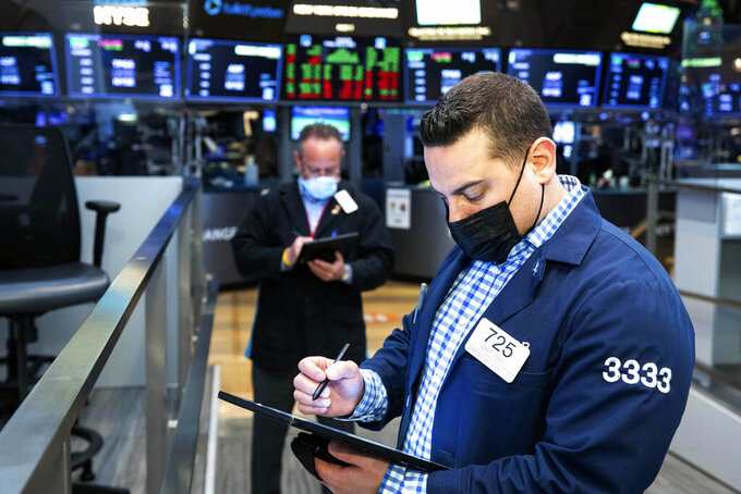 In this photo provided by the New York Stock Exchange, Adam Logan, foreground, works with a fellow trader on the floor, Friday, April 9, 2021. Technology companies helped lift stocks higher on Wall Street in afternoon trading Friday, placing the market within striking distance of more record highs. (Colin Ziemer/New York Stock Exchange via AP)