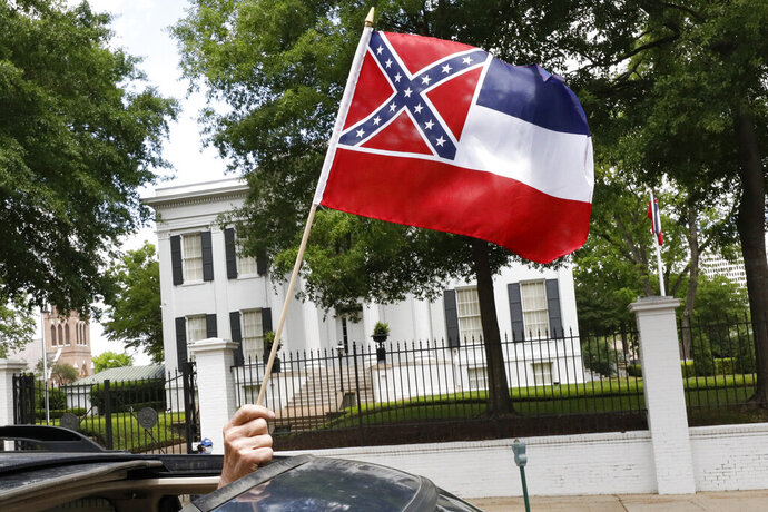 In this April 25, 2020 photograph, a small Mississippi state flag is held by a participant during a drive-by