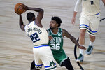 Milwaukee Bucks' Khris Middleton (22) looks to pass around Boston Celtics' Marcus Smart (36) during the first half of an NBA basketball game Friday, July 31, 2020, in Lake Buena Vista, Fla. (AP Photo/Ashley Landis, Pool)