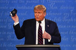 President Donald Trump holds up his face mask during the first presidential debate Tuesday, Sept. 29, 2020, at Case Western University and Cleveland Clinic, in Cleveland, Ohio. (AP Photo/Julio Cortez)